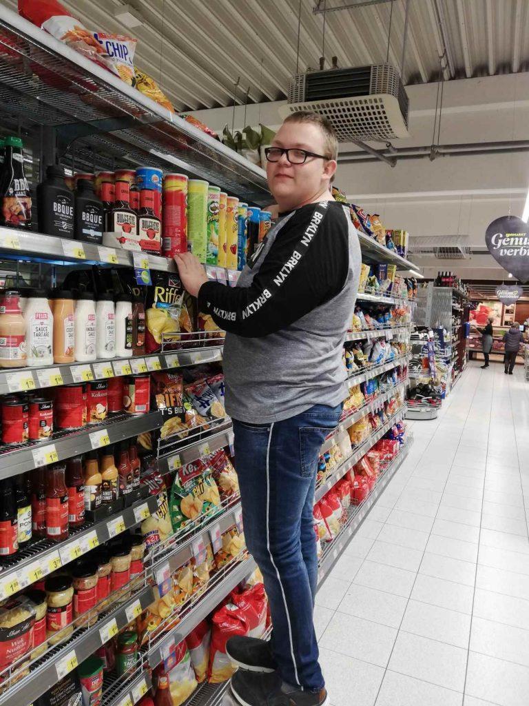 Ein junger Mann räumt im Supermarkt die Regale ein